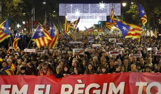 Protesters hold a banner that reads in Catalan ''Knock down the regime'' during a rally in Barcelona, Spain, Friday, Dec. 21, 2018. Thousands of pro-independence protesters angry about Spain's Cabinet holding a meeting in Catalonia blocked roads across the region Friday and clashed with anti-riot police in its capital. (AP Photo/Emilio Morenatti)