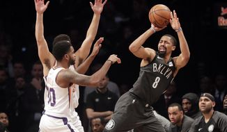 Brooklyn Nets' Spencer Dinwiddie (8) passes away from Phoenix Suns' Troy Daniels (30) during the first half of an NBA basketball game Sunday, Dec. 23, 2018, in New York. (AP Photo/Frank Franklin II)