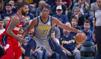 Indiana Pacers center Myles Turner (33) works the ball toward the basket against the defense of Washington Wizards forward Markieff Morris (5) during an NBA basketball game, Sunday, Dec. 23, 2018, in Indianapolis. (AP Photo/Doug McSchooler)