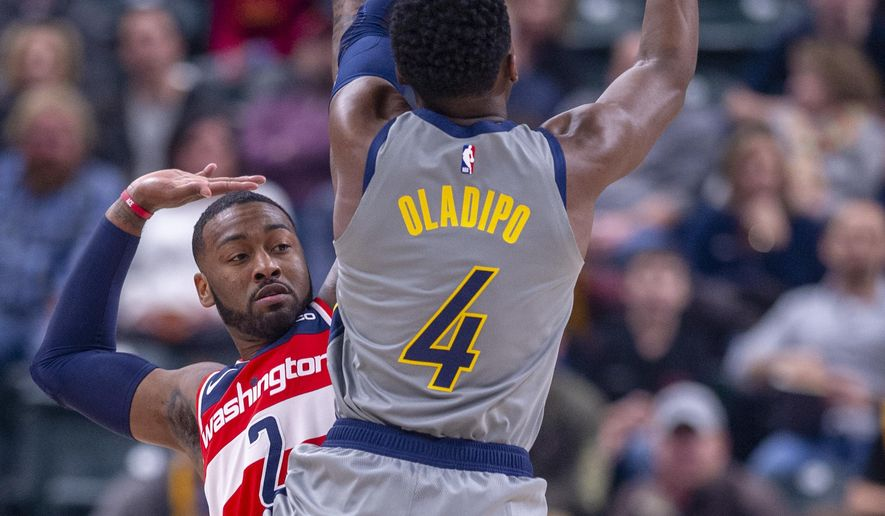Indiana Pacers guard Victor Oladipo (4) collides with Washington Wizards guard John Wall (2) as he shoots during an NBA basketball game, Sunday, Dec. 23, 2018, in Indianapolis. (AP Photo/Doug McSchooler)