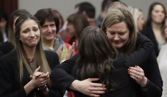 FILE -In this Jan. 24, 2018, file photo, victims react and hug Assistant Attorney General Angela Povilaitis after Larry Nassar was sentenced by Judge Rosemarie Aquilina to 40 to 175 years in prison during a sentencing hearing in Lansing, Mich. (AP Photo/Carlos Osorio, File) **FILE**