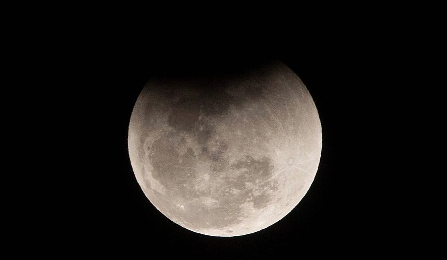 The moon passes into the earth's shadow during a lunar eclipse as seen in Gauhati, India, Wednesday, Jan. 31, 2018. (AP Photo/Anupam Nath)