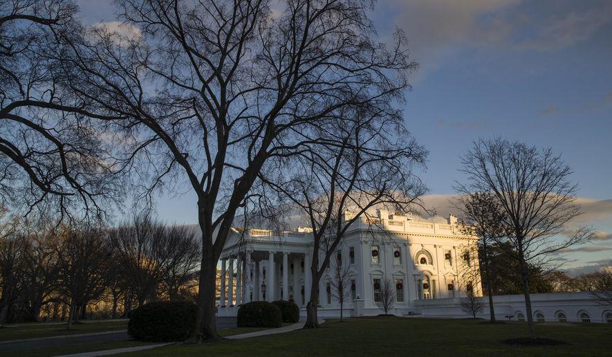 The setting sun illuminates the White House. (AP Photo/Alex Brandon)