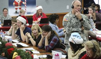 In this Dec. 24, 2014, photo, NORAD Chief of Staff Maj. Gen. Charles D. Luckey takes a call while volunteering at the NORAD Tracks Santa center at Peterson Air Force Base in Colorado Springs, Colo. Hundreds of volunteers will help answer the phones from children around the world calling for Santa when the program resumes on Monday, Dec. 24, 2018, for the 63rd year. (AP Photo/Brennan Linsley) **FILE**