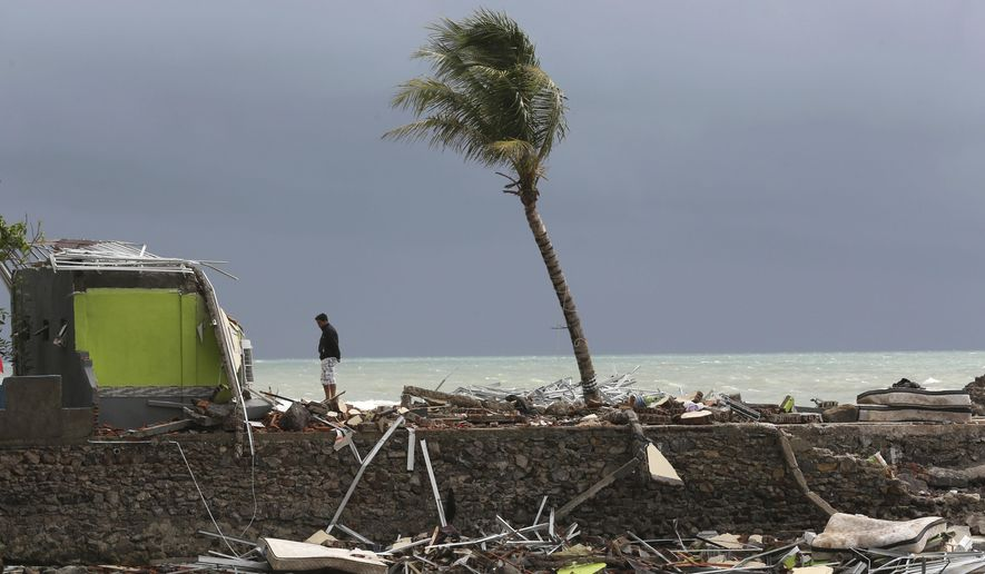 A man stands on the debris following a tsunami in Carita beach, Indonesia, Monday, Dec. 24, 2018. Doctors worked to save injured victims while hundreds of military and volunteers scoured debris-strewn beaches in search of survivors Monday after a deadly tsunami gushed ashore without warning on Indonesian islands on a busy holiday weekend. (AP Photo/Tatan Syuflana)