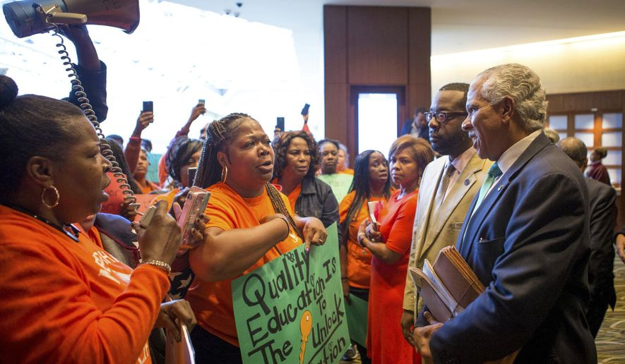 This Oct. 15, 2016, file photo shows parents and grandparents from Memphis Lift speaking to Hilary Shelton, the director to the NAACP's Washington Bureau and senior vice president for Advocacy and Policy, during the national NAACP board meeting in downtown Cincinnati. While some black leaders see charters as a safer, better alternative in their communities, a deep rift of opinion was exposed by a 2016 call for a moratorium on charters by the NAACP, a longtime skeptic that expressed concerns about school privatization and accountability issues surrounding charters. (The Cincinnati Enquirer via AP)