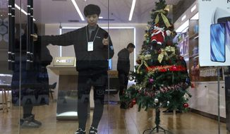 In this Saturday, Dec. 22, 2018, photo, a sales person waits for customers near a Christmas tree decoration in Zhangjiakou in northern China's Hebei province. At least three Chinese cities have banned Christmas decorations this year. Churches in another city have been warned to keep minors away from Christmas, and at least ten schools nationwide have curtailed Christmas on campus, The Associated Press has found. (AP Photo/Ng Han Guan)