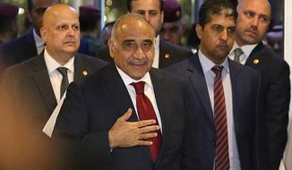 "FILE - In this Oct. 24, 2018 file photo, then Prime Minister-designate Adel Abdul-Mahdi, center, arrives to the parliament building, in the heavily guarded Green Zone, in Baghdad, Iraq. Abdul-Mahdi told reporters at a press conference on Monday, Dec. 24, 2018, that his government could deploy troops inside Syria, in the latest fallout from the U.S. decision to withdraw from the war-torn country. The prime minister said his government is ""considering all the options"" to protect Iraq from threats across its borders. (AP Photo/Hadi Mizban, File)"