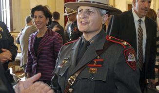FILE - In this Nov. 3, 2016, file photo, Rhode Island Gov. Gina Raimondo, left, stands beside Ann C. Assumpico, center, whom she named as the 13th Superintendent of the Rhode Island State Police during a ceremony at the State House, in Providence, R.I. Assumpico, who was the first women to lead the State Police, announced Monday, Dec. 24, 2018, she will retire in January of 2019. (Steve Szydlowski/Providence Journal via AP, File)