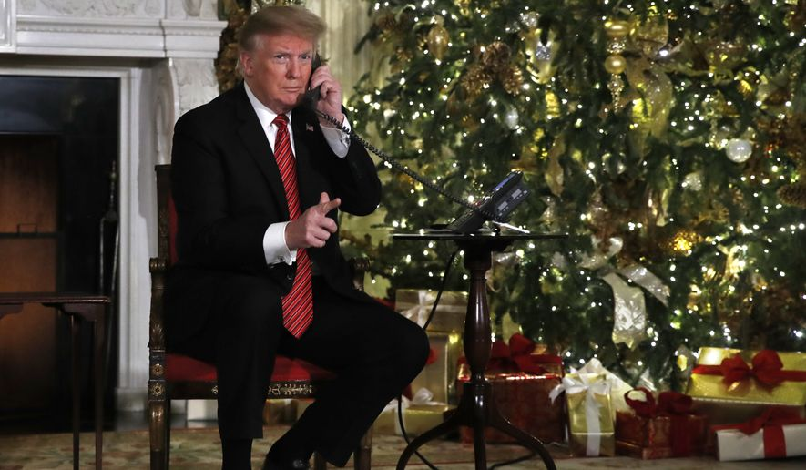 President Donald Trump gestures toward members of the media as he and first lady Melania Trump both speak on the phone to share updates tracking Santa's movements from the North American Aerospace Defense Command (NORAD) Santa Tracker on Christmas Eve, Monday, Dec. 24, 2018. (AP Photo/Jacquelyn Martin)
