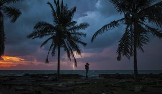 A photojournalist is silhouetted by the sunset as a lightning strike at a resort affected by Saturday's tsunami in Carita, Indonesia, Tuesday, Dec. 25, 2018. Christmas celebrations traditionally filled with laughter and uplifting music were replaced by somber prayers for tsunami victims in an area hit without warning following a volcanic eruption, leaving hundreds of people dead and thousands homeless in disaster-prone Indonesia. (AP Photo/Fauzy Chaniago)