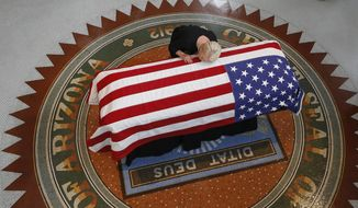 FILE - In this Aug. 29, 2018, file photo, Cindy McCain, wife of U.S. Sen. John McCain, places her head on her husband's casket at a private memorial service at the Arizona Capitol in Phoenix. The death of McCain after a yearlong battle with brain cancer was the top story of the year in Arizona. (AP Photo/Ross D. Franklin, File)