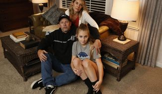 FILE - In this Nov. 26, 2018 file photo Jason James Burnett, accompanied by his daughter Faith and wife, Heather, poses at his mother-in-law's home in Chico, Calif. Burnett who lost her home in California's most destructive wildfire ever says she and her husband are humbled to have received pardons from Gov. Jerry Brown for old drug crimes. Burnett said Tuesday, Dec. 25, 2018, the pardons were bright spots in what has been a difficult period. Brown on Monday wiped away her conviction for possessing ephedrine with intent to make methamphetamine nearly 20 years after she was sentenced for the crime. (AP Photo/Rich Pedroncelli,File)