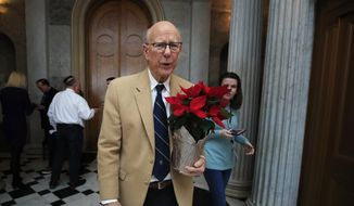 Sen. Pat Roberts, R-Kan., carries a poinsettia on Capitol Hill in Washington, Monday, Dec. 24, 2018, after a pro forma session, a brief meeting of the Senate, during a partial government shutdown. (AP Photo/Manuel Balce Ceneta) ** FILE **