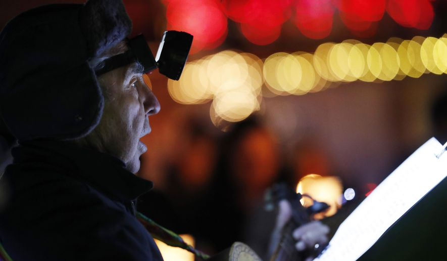 In this Monday, Dec. 24, 2018, photograph, Phil Baca plays a guitar and sings during a Christmas Eve candlelight vigil and a tradition called Las Posadas, where churchgoers re-enact Mary and Joseph's search for a place to stay in Bethlehem, at Our Lady of Visitation Church in Denver. Members of the Denver Catholic church built by Hispanic families are fighting to re-open their parish over a year after it was closed by the archbishop. (AP Photo/David Zalubowski)