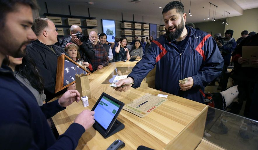 FILE - In this Nov. 20, 2018 file photo, Stephen Mandile, right, an Iraq War veteran from Uxbridge, Mass., is the first to purchase recreational marijuana at the Cultivate dispensary in Leicester, Mass., on the first day of legal sales in Massachusetts. Voters approved it in 2016, but the start of recreational marijuana sales was among the tops stories in the state in 2018. (AP Photo/Steven Senne, File)