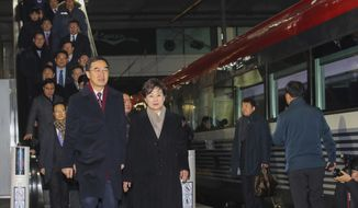 South Korean Unification Minister Cho Myoung-gyon, bottom left, and officials arrive to board a train to leave for the North Korea at the Seoul Railway Station in Seoul, South Korea, Wednesday, Dec. 26, 2018. South Korean officials have traveled to North Korea by train to attend a groundbreaking ceremony for an aspirational project to modernize North Korean railways and roads and connect them with the South. (Jin Sung-chul/Yonhap via AP)