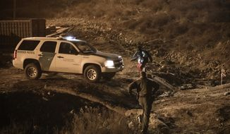 A border patrol officer fails to arrest a migrant running after jumping the United States border fence to San Diego, from Tijuana, Mexico, Tuesday, Dec. 25, 2018. Discouraged by the long wait to apply for asylum through official ports of entry, many Central American migrants from recent caravans are choosing to cross the U.S. border wall and hand themselves into border patrol agents. (AP Photo/Daniel Ochoa de Olza)