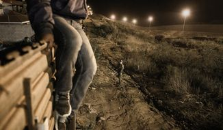 A migrant jumps into the United States to San Diego, from Tijuana, Mexico, in front of a border patrol officer on Tuesday, Dec. 25, 2018. Discouraged by the long wait to apply for asylum through official ports of entry, many Central American migrants from recent caravans are choosing to cross the U.S. border wall and hand themselves into border patrol agents. (AP Photo/Daniel Ochoa de Olza)