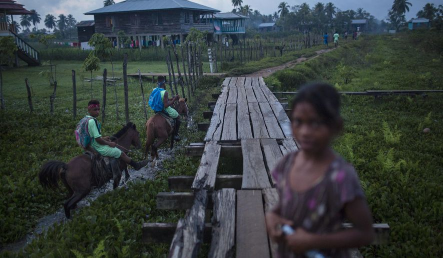In this Sept. 1, 2018 photo, men ride past on their horses, in Irlaya, Honduras. Among exotic, tropical vegetation along the Caribbean coast, the Mosquitia region is sprinkled with small fishing villages where residents live in clapboard houses.. (AP Photo/Rodrigo Abd)