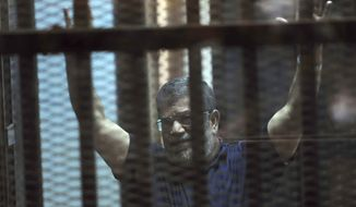 FILE - In this May 16, 2015 file photo, ousted Egyptian President Mohammed Morsi raises his hands as he sits behind glass in a courtroom, at the national police academy in a Cairo suburb, Egypt. On Wednesday, Dec. 26, 2018, two former Egyptian presidents appeared in the same Cairo courtroom. The 90-year-old Mubarak testified in a retrial of Mohammed Morsi. Mubarak whose nearly three-decade rule was ended by a popular uprising in 2011, was seen walking into the courtroom with a cane along with his two sons Alaa and Gamal. (AP Photo/Ahmed Omar, File)
