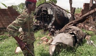 ** FILE ** A Rwanda Patriotic Front (RPF) rebel walks by the the site of a April 6 plane crash which killed Rwanda's President Juvenal Habyarimana in this May 23, 1994 file photo in Kigali. French authorities have dropped a sensitive, long-running investigation into the plane crash that sparked Rwanda's 1994 genocide, citing lack of sufficient evidence. Several people close to Rwanda's current president, Paul Kagame, had been under investigation in the case. The cause of the crash has been a contentious issue. The plane had a French crew, and Rwanda has long accused France of complicity in the genocide, which France denies. (AP Photo/Jean Marc Bouju)