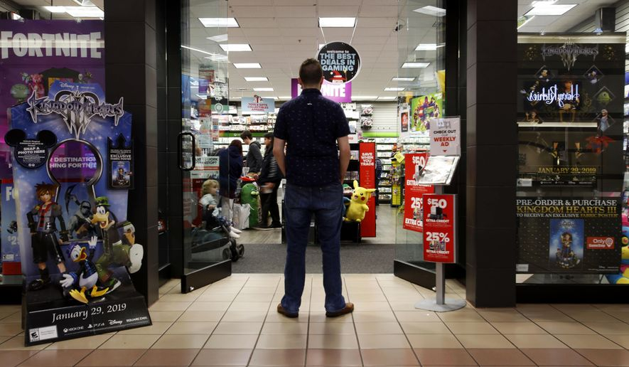 """In this Dec. 9, 2018 photo, a 27-year-old self-described tech addict poses for a portrait in front of a video game store at a mall in Everett, Wash. He asked to remain anonymous because he works in the tech industry and fears that speaking out about the negatives of excessive tech use could hurt his career. """"If we get to a point in the tech industry where I can use my name and show my face in cases like this, thence've gotten somewhere. That'll be a turning point."""" (AP Photo/Martha Irvine)"""