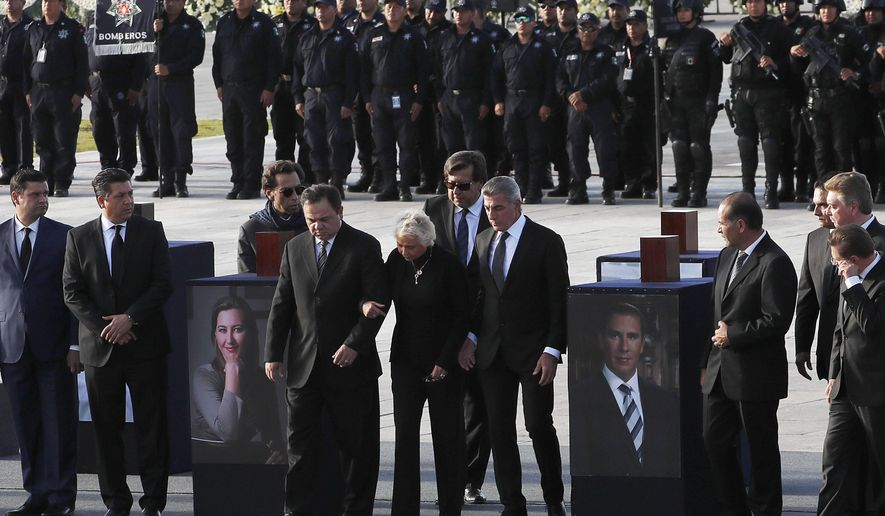 Mexico's Secretary of the Interior Olga Sanchez Cordero, center, stands between urns with ashes of Puebla state Gov. Martha Erika Alonso, left, and her husband, ex-Puebla Gov. Rafael Moreno Valle, during a farewell ceremony in Puebla City, southeast of Mexico, Tuesday, Dec. 25, 2018. Mexico has invited experts from the U.S. National Transportation Safety Board to investigate a helicopter crash that killed the governor, her husband, two pilots and a third passenger. (AP Photo/Marco Ugarte)