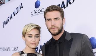 "In this Aug. 8, 2013, file photo, actor Liam Hemsworth and singer and actress Miley Cyrus arrive on the red carpet at the U.S. premiere of the feature film ""Paranoia"" at the DGA Theatre in Los Angeles. Cyrus and Hemsworth have tied the knot amid reports the couple got married in a secret wedding ceremony. Cyrus posted three black-and-white photos of her and Hemsworth on the singer's Instagram and Twitter accounts on Wednesday, Dec. 26, 2018. (Photo by Dan Steinberg/Invision/AP, File)"