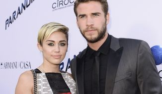 "Actor Liam Hemsworth and singer and actress Miley Cyrus arrive on the red carpet at the U.S. premiere of the feature film ""Paranoia"" at the DGA Theatre in Los Angeles, Aug. 8, 2013. Cyrus and Hemsworth have tied the knot amid reports the couple got married in a secret wedding ceremony. Cyrus posted three black-and-white photos of her and Hemsworth on the singer's Instagram and Twitter accounts on Wednesday, Dec. 26, 2018. (Photo by Dan Steinberg/Invision/AP) ** FILE **"
