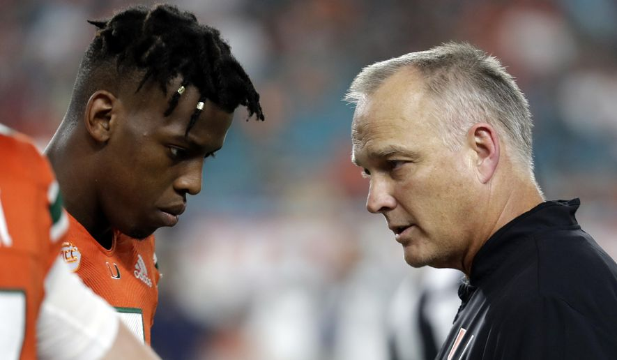 File-This Nov. 24, 2018, file photo shows Miami quarterback N'Kosi Perry, left, talking with Miami head coach Mark Richt during the second half of an NCAA college football game against Pittsburgh, in Miami Gardens, Fla.   The Hurricanes could play the Pinstripe Bowl without Perry in the wake of a sexually explicit video he posted on Snapchat. The video appeared to have been filmed in September but recently resurfaced and could cost Perry (1,089 yards passing, 13 touchdowns) a Pinstripe start. Malik Rosier, who started six games this season before he was replaced by Perry, will likely get the start. Jarren Williams could also get some snaps for the Hurricanes. Richt had not announced a starter on Wednesday. (AP Photo/Lynne Sladky, File)
