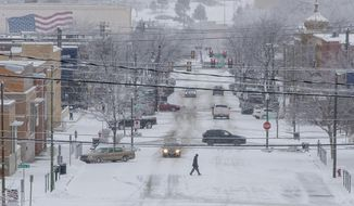 A pedestrian crosses Seventh Street in downtown Rapid City, S.D., on Wednesday, Dec. 26, 2018. Forecasters say a post-Christmas winter storm could dump more than a foot of snow on parts of the Dakotas and Minnesota in the next several days. (Ryan Hermens/Rapid City Journal via AP)