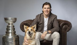 Washington Capitals forward T.J. Oshie poses with a dog and the Stanley Cup during the team's 2019 Caps Canine Calendar photo shoot. (Photo by Virgil Ocampo Photography / courtesy of Washington Capitals)