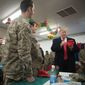 President Trump signs a Make America Great Again hat as he visits with members of the military at a dining hall at Al Asad Air Base, Iraq, on Wednesday. A former Pentagon spokesman blasted both Mr. Trump and the soldier for event. (Associated Press)