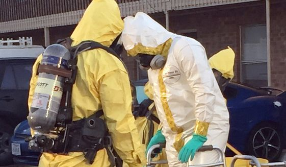 In this Thursday, Oct. 27, 2016, file photo provided by the U.S. Drug Enforcement Agency, members of the DEA Hazardous Materials/Clandestine Laboratory Enforcement Team go through a decontamination procedure in Lubbock, Texas. During the operation, substances were seized during an ongoing investigation of fentanyl and fentanyl-related compounds. (Russ Baer/DEA via AP) ** FILE **