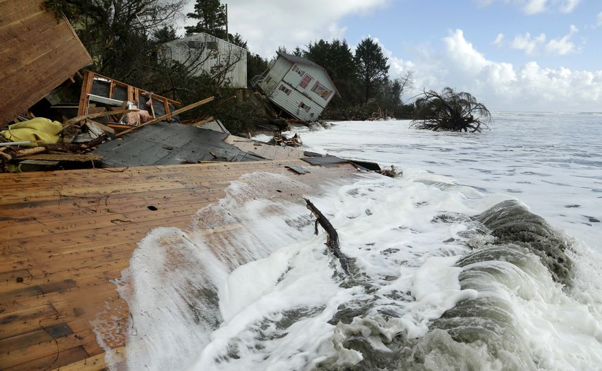Waves break on the remains of a structure as a house that toppled over the eroding Pacific Ocean shoreline of North Cove, Wash., is shown in the background. (AP Photo/Ted S. Warren, File)