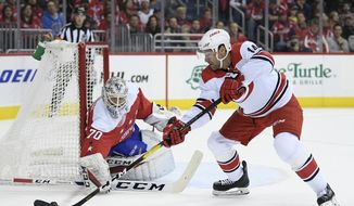 Carolina Hurricanes right wing Justin Williams (14) skates with the puck against Washington Capitals goaltender Braden Holtby (70) during the first period of an NHL hockey game, Thursday, Dec. 27, 2018, in Washington. (AP Photo/Nick Wass)