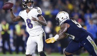 FILE - In this Dec. 23, 2018, file photo, Baltimore Ravens quarterback Lamar Jackson looks to pass during the first half of the team's NFL football game against the Los Angeles Chargers in Carson, Calif. In November, Baltimore underwent a transformation even more radical than the Cleveland Browns'. Rookie Jackson took over at quarterback, the defense stiffened, and the Ravens used a 5-1 streak to overtake Pittsburgh last week and move into first place. Now, Baltimore is poised to end its three-year hiatus from the playoffs. The Ravens play the Cleveland Browns this week. (AP Photo/Kelvin Kuo, File)
