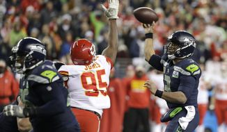 Seattle Seahawks quarterback Russell Wilson, right, passes under pressure by Kansas City Chiefs defensive end Chris Jones (95) during the second half of an NFL football game, Sunday, Dec. 23, 2018, in Seattle. The Seahawks won 38-31. (AP Photo/Elaine Thompson)