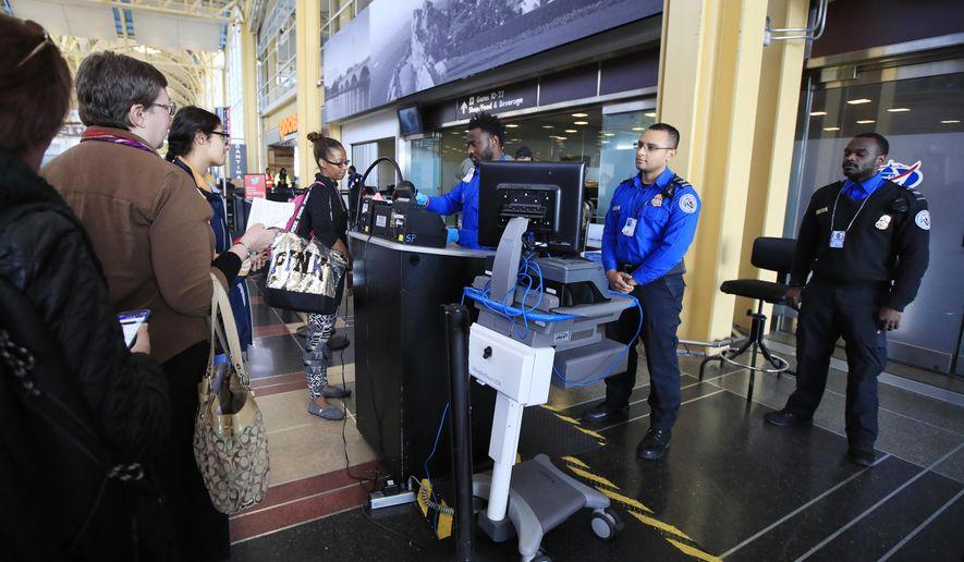 Transportation Security Administration (TSA) officers check and watch airline passengers at Reagan National Airport in Washington, Thursday, Dec. 27, 2018. (AP Photo/Manuel Balce Ceneta)