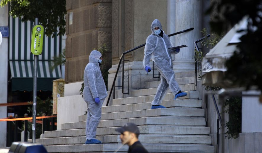Greek forensic experts search at the scene after an explosion outside the Orthodox church of Agios Dionysios in the upscale Kolonaki area of Athens, Thursday, Dec. 27, 2018. A Greek police officer and a church caretaker were injured in an explosion as they investigated a suspicious package outside a church in central Athens early Thursday. (AP Photo/Thanassis Stavrakis)