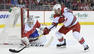 Carolina Hurricanes right wing Justin Williams (14) skates with the puck against Washington Capitals goaltender Braden Holtby (70) during the first period of an NHL hockey game, Thursday, Dec. 27, 2018, in Washington. (AP Photo/Nick Wass) ** FILE **