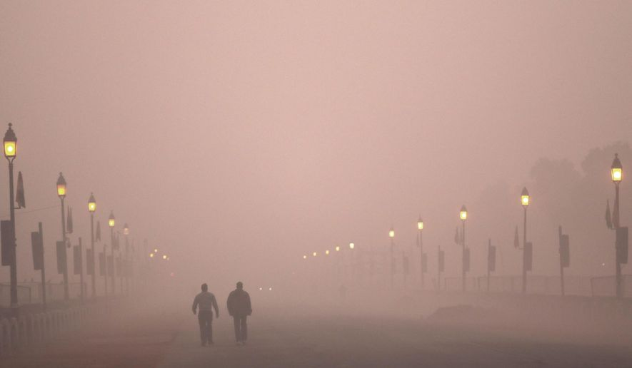 In this Wednesday, Dec. 26, 2018, photo, people take early morning walk amidst smog in New Delhi, India. Authorities have ordered fire services to sprinkle water from high rise building to settle dust particles and stop burning of garbage and building activity in the Indian capital as the air quality hovered between severe and very poor this week posing a serious health hazard for millions of people. (AP Photo/Manish Swarup)