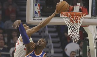 Milwaukee Bucks' Giannis Antetokounmpo, left, tries to dunk over New York Knicks' Noah Vonieh during the first half of an NBA basketball game Thursday, Dec. 27, 2018, in Milwaukee. (AP Photo/Jeffrey Phelps)