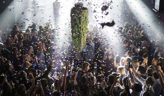 In this Oct. 17, 2018, file photo a depiction of a cannabis bud drops from the ceiling at Leafly's countdown party in Toronto as midnight passes and marks the first day of the legalization of cannabis across Canada. The last year was a 12-month champagne toast for the legal marijuana industry as the global market exploded and cannabis pushed its way further into the financial and cultural mainstream. Canada ushered in broad legalization, U.S. drug regulators approved the first cannabis-based drug and investors pumped in billions of dollars. (Chris Young/The Canadian Press via AP, File)