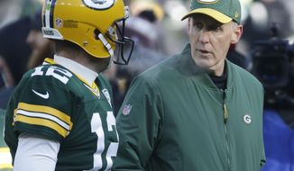 FILE - In this Dec. 9, 2018, file photo, Green Bay Packers interim head coach Joe Philbin talks to Aaron Rodgers before an NFL football game against the Atlanta Falcons in Green Bay, Wis. The Detroit Lions and Packers will each try to wrap up disappointing seasons overall with a win when they face off at Lambeau Field on Sunday, Dec. 30. (AP Photo/Mike Roemer, File)