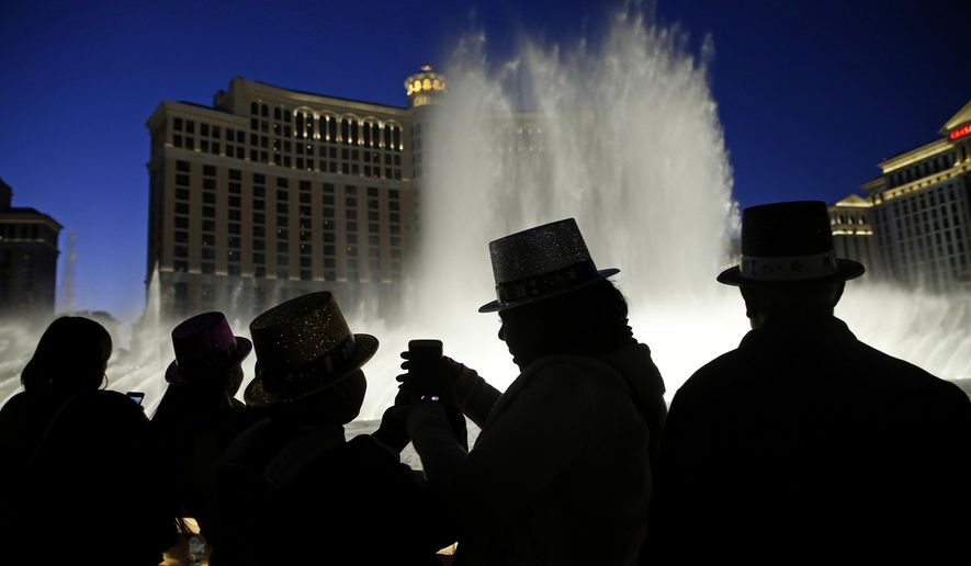 FILE - In this Dec. 31, 2015, file photo, people watch the fountains at the Bellagio while wearing paper hats to celebrate New Years Eve in Las Vegas. Las Vegas will usher in 2019 trying to outdo itself with performances by Lady Gaga, Gwen Stefani, Bruno Mars and other superstars at the city's various venues. More than 300,000 people are expected to gather Monday, Dec. 31, 2018, on the world-famous Las Vegas Strip to watch 8 minutes of fireworks. (AP Photo/John Locher, File)