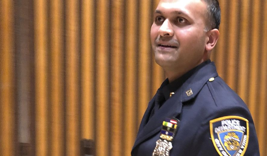 New York City police officer Syed Ali walks out of a briefing room at police headquarters, Thursday, Dec. 27, 2018, after speaking to reporters about his battle with three homeless men who came at him as he patrolled a Manhattan subway station on Sunday, Dec. 22. Ali has been widely praised for his response, which was caught on a video that has gone viral. Charges were brought against Ali's assailants after the video of the attack was viewed more than 4.75 million times on social media. (AP Photo/Michael R. Sisak)