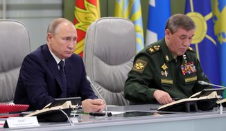 Russian President Vladimir Putin, left, and Chief of General Staff of Russia Valery Gerasimov oversee the test launch of the Avangard hypersonic glide vehicle from the Defense Ministry's control room in Moscow, Russia, Wednesday, Dec. 26, 2018. In the test, the Avangard was launched from the Dombarovskiy missile base in the southern Ural Mountains. The Kremlin says it successfully hit a designated practice target on the Kura shooting range on Kamchatka, 6,000 kilometers (3,700 miles) away. (Mikhail Klimentyev, Sputnik, Kremlin Pool Photo via AP)