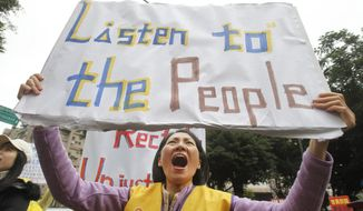 A protester shouts slogans demanding tax reform outside the Ministry of Finance in Taipei, Taiwan, Thursday, Dec. 27, 2018. A large group of activists has launched anti-government protests to demand tax reform - after being inspired by the violent demonstrations in Paris that began last month. (AP Photo/Chiang Ying-ying)